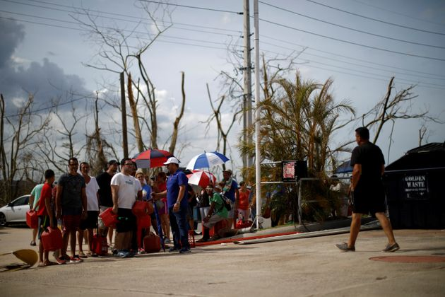 People queue to fill containers with gasoline at a gas station after the area was hit by Hurricane...