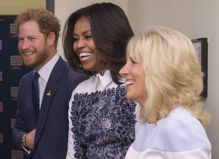 Holding his stomach Wwith Michelle Obama and Jill Biden at the Invictus Games in 2015.