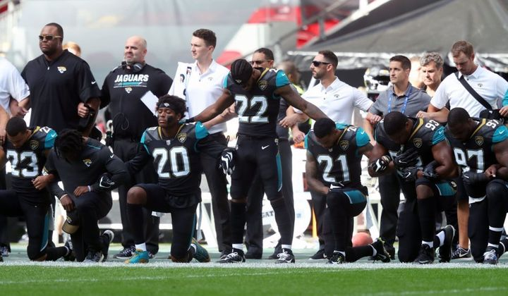 NFL players protest racial injustice by kneeling and locking arms during national anthem.