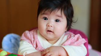 infant in close up placing her hand in front,looking at the camera