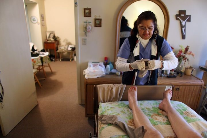 A home-care worker in Miami helps her client get dressed.