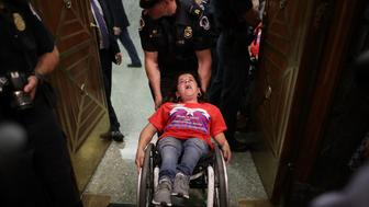 WASHINGTON, DC - SEPTEMBER 25:  U.S. Capitol Police arrest protesters from handicap advocacy organizations as they shout and interrupt a Senate Finance Committee hearing about the proposed Graham-Cassidy Healthcare Bill in the Dirksen Senate Office Building on Capitol Hill September 25, 2017 in Washington, DC. Demonstrators disrupted the hearing to protest the legislation, the next in a series of Republican proposals to replace the Affordable Care Act, also called Obamacare.  (Photo by Chip Somodevilla/Getty Images)