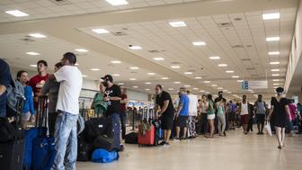 Travelers stand in line at Luis Muoz Marn International Airport in San Juan, Puerto Rico, on Monday, Sept. 25, 2017. Hurricane Maria hit the Caribbean island last week, knocking out electricity throughout the island. The territory is facing weeks, if not months, without service as utility workers repair power plants and lines that were already falling apart. Photographer: Alex Wroblewski/Bloomberg via Getty Images
