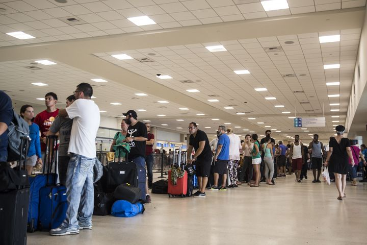Travelers stand in line at Luis Muoz Marn International Airport in San Juan, Puerto Rico, on Monday.