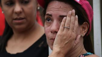 HAYALES DE COAMO, PUERTO RICO - SEPTEMBER 24: Lizzy Alicea wipes away tear as she sees her after traveling from San Juan to check on her because she couldn't get through on the telephone after Hurricane Maria passed through the area on September 24, 2017 in Hayales de Coamo, Puerto Rico.  Puerto Rico experienced widespread damage after Hurricane Maria, a category 4 hurricane, passed through.  (Photo by Joe Raedle/Getty Images)