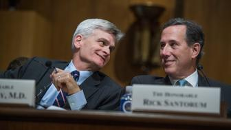 UNITED STATES - SEPTEMBER 25: Sen. Bill Cassidy, R-La., and former Sen. Rick Santorum, R-Pa., confer during a Senate Finance Committee hearing on the proposal by Cassidy and Sen. Lindsey Graham, R-S.C., to repeal and replace the Affordable Care Act on September 25, 2017. (Photo By Tom Williams/CQ Roll Call)