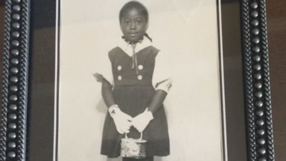 A childhood photo shows a young Trilby Barnes smiling and holding a purse.