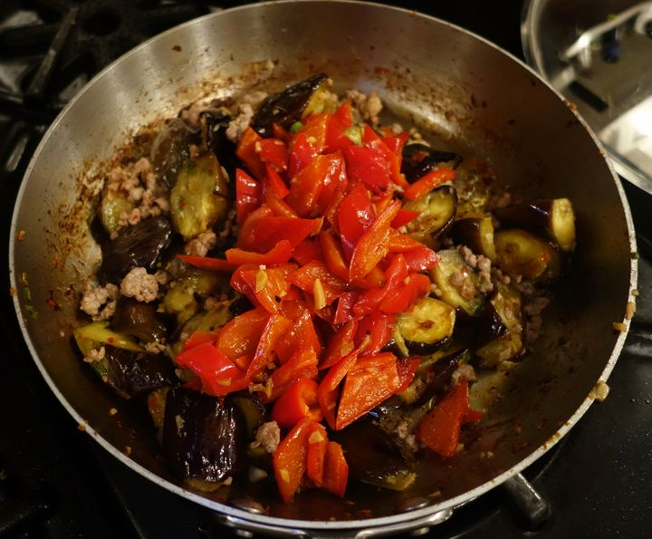 When the eggplant is tender, return the meat to the pan, then the peppers