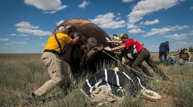 Russian support personnel roll the Soyuz TMA-19M spacecraft after it landed with Expedition 47 crew members...