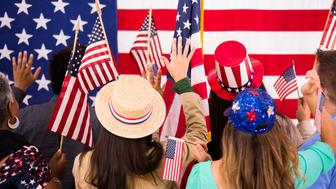Multi-ethnic and mixed ages group excitedly wave their American flags at Republican or Democratic political rally or national convention. Primary and presidential election/voting concepts.