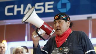 Raymond Kingfisher speaks as indigenous leaders and climate activists disrupt business at a Chase Bank branch to protest funding tar sands development and projects like the Keystone XL pipeline, in Seattle, Washington on May 8, 2017.  / AFP PHOTO / Jason Redmond        (Photo credit should read JASON REDMOND/AFP/Getty Images)