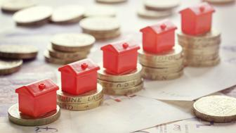 Minature houses resting on pound coin stacks concept for property ladder, mortgage and real estate investment