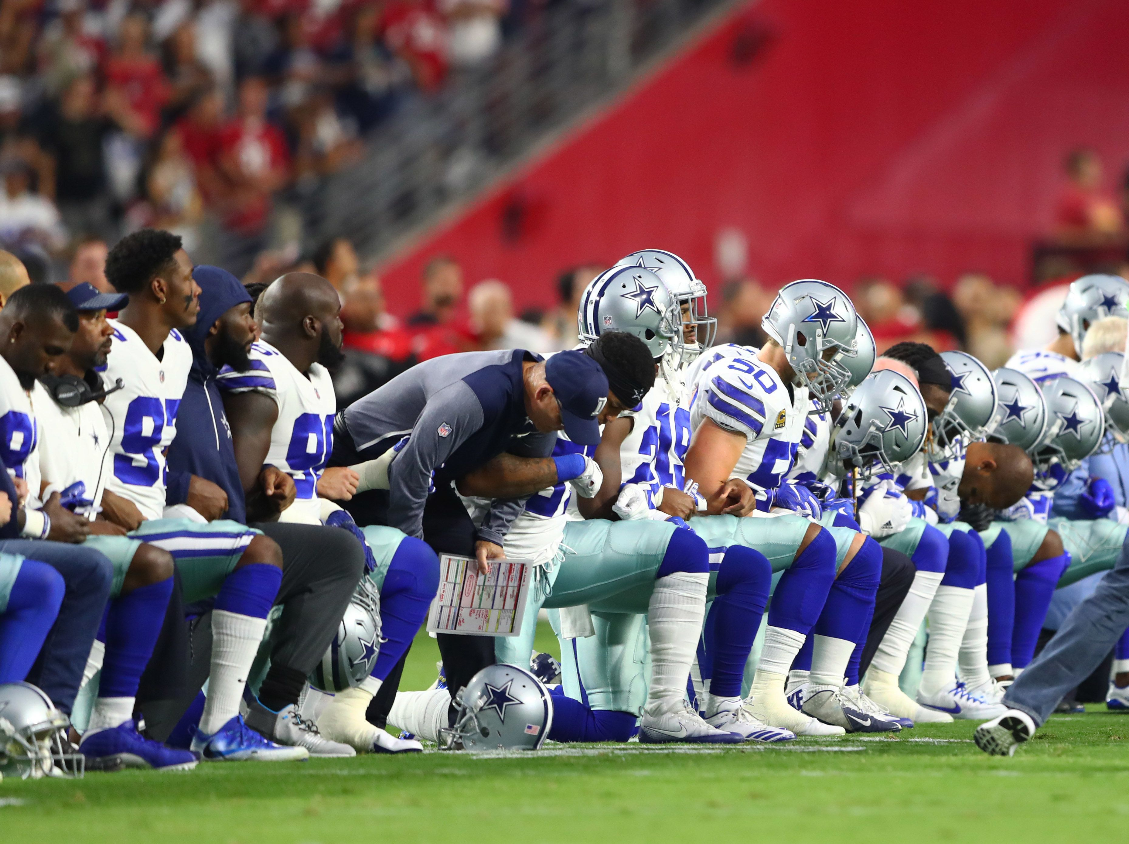 Sep 25, 2017; Glendale, AZ, USA; Dallas Cowboys players kneel together with their arms locked prior to the game against the Arizona Cardinals at University of Phoenix Stadium. Mandatory Credit: Mark J. Rebilas-USA TODAY Sports