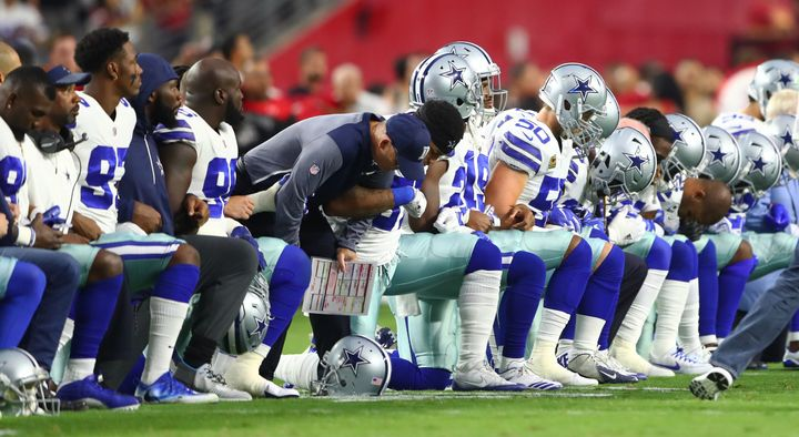 Dallas Cowboys players kneel together with their arms locked prior to the game against the Arizona Cardinals at University of