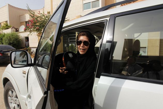 Azza Al Shmasani alights from her car after driving in defiance of the ban in Riyadh on June 22,
