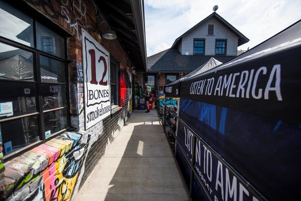 A sign for 12 Bones Smokehouse appears across from the HuffPost video activation site in Asheville.