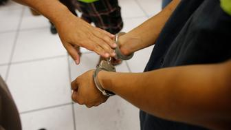 Cameron County sheriff's officer puts handcuffs on a suspected illegal immigrant caught with marijuana during a traffic stop in south Texas. (Photo by Robert Daemmrich Photography Inc/Corbis via Getty Images)
