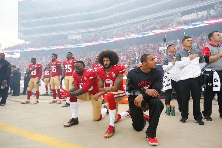 Eli Harold #58, Colin Kaepernick #7 and Eric Reid #35 of the San Francisco 49ers kneel on the sideline, during the anthem, pr
