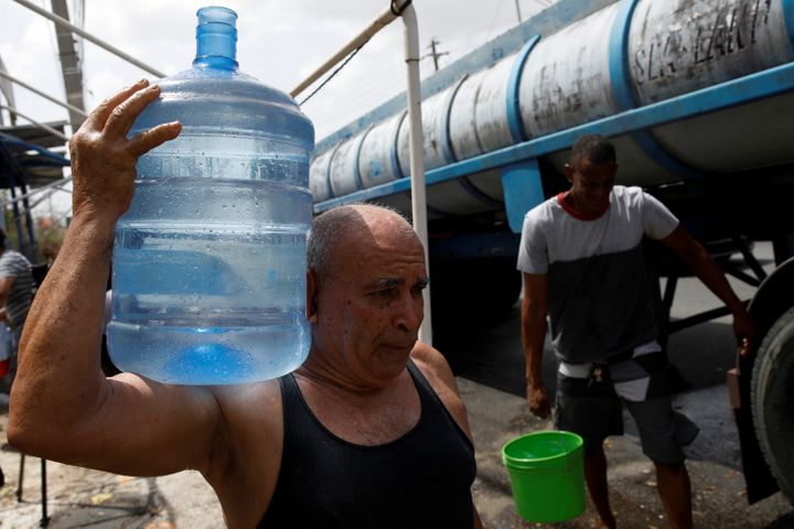 Men carry containers filled with water from a tank truck in the municipality of Canovanas, Puerto Rico, on Sept. 26.