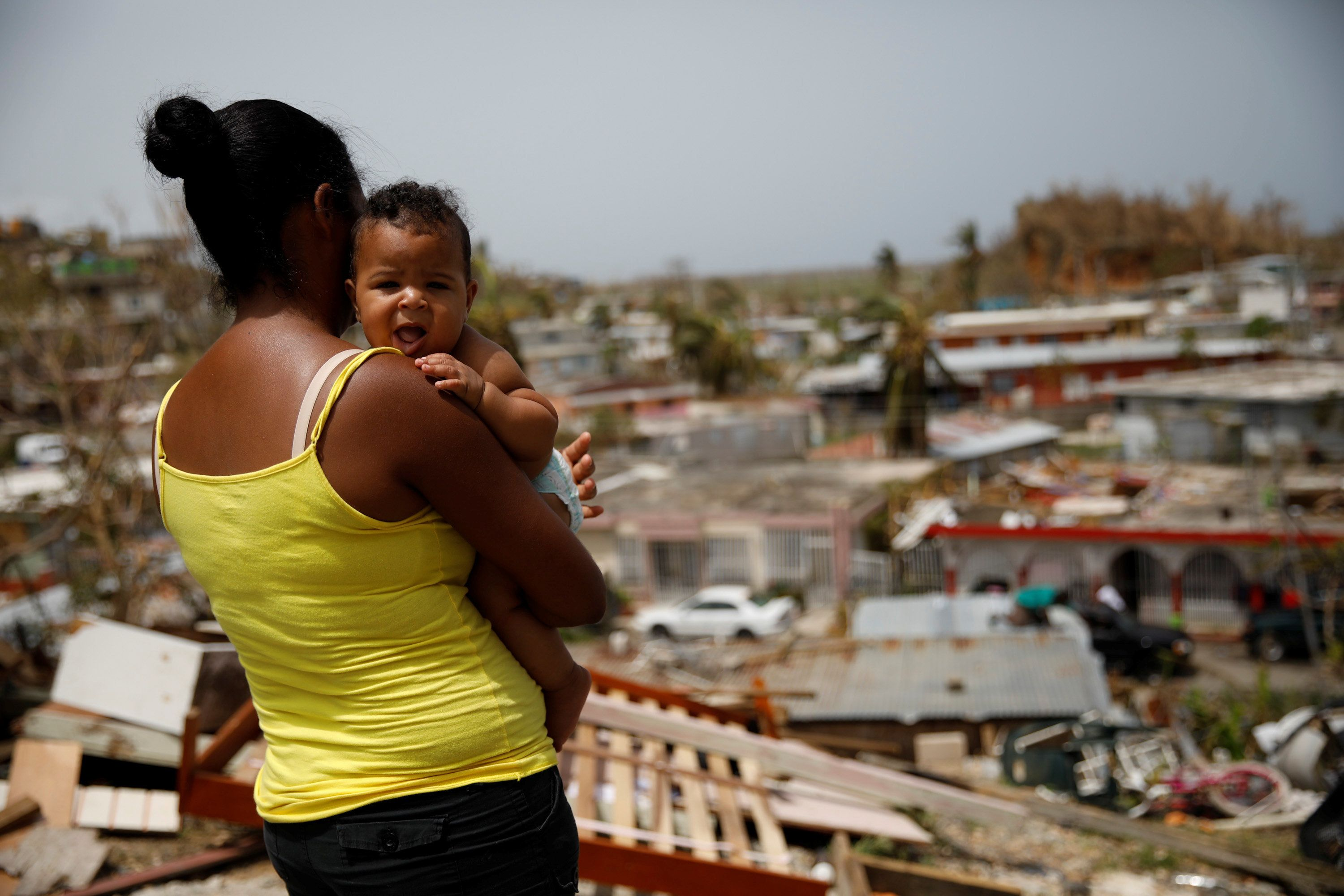 A woman carrying her baby looks at the damage in Canovanas on Sept. 26.