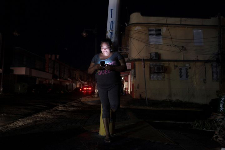 A woman uses her cell phone on a San Juan, Puerto Rico, street during a blackout on Sept. 25.