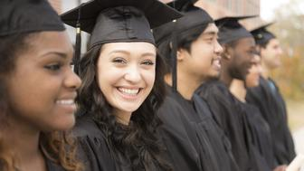 Six multi-ethnic friend graduates excitedly wait for their name to be called during graduation ceremony. Mixed-race girl looks back at camera. School building background.