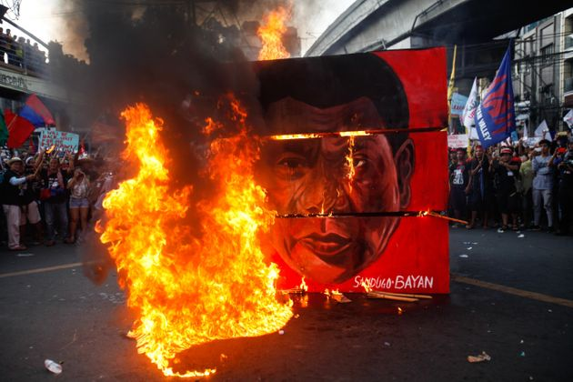 A cubic effigy painted with the face of President Rodrigo Duterte is set on fire by activists during...