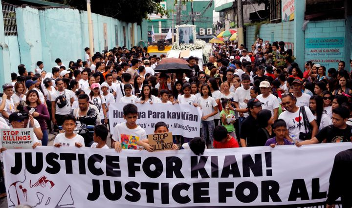 Mourners display a streamer during a funeral march for Kian delos Santos, a 17-year-old student who was killed in Caloocan, P