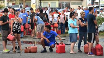 People wait in line to purchase petrol in Arecibo, northwestern Puerto Rico, on September 22, 2017  in the aftermath of Hurricane Maria.  Puerto Rico Governor Ricardo Rossello called Maria the most devastating storm in a century after it destroyed the US territory's electricity and telecommunications infrastructure.  / AFP PHOTO / HECTOR RETAMAL        (Photo credit should read HECTOR RETAMAL/AFP/Getty Images)