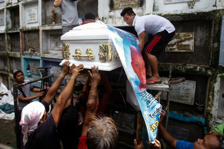 The body of slain teenager Reynaldo De Guzman is laid to rest at a cemetery during funeral rites in suburban Pasig City, east
