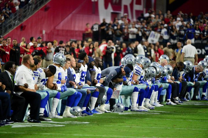 The Dallas Cowboys players, coaches and staff take a knee prior to standing for the National Anthem during a game against the
