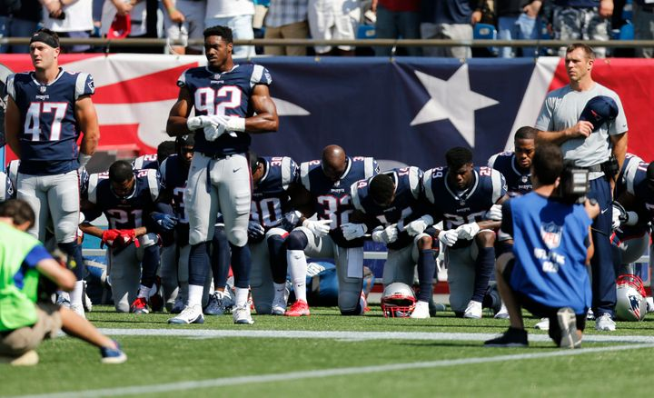 Members of the New England Patriots take a knee during the national anthem before a game against the Houston Texans at Gillet