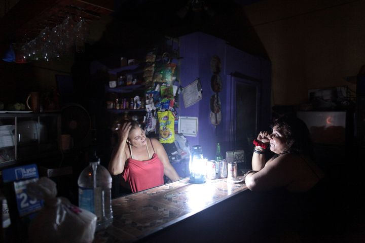 Flor Dalisa Contreras, left, talks with Virginia Rivas at a coffee shop during a power outage in San Juan, Puerto Rico, last