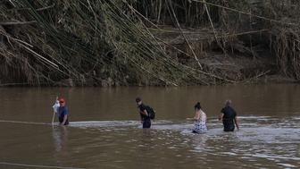 MOROVIS, PUERTO RICO - SEPTEMBER 27:  People cross a river on foot after the bridge was washed away when Hurricane Maria passed through on September 27, 2017 in Morovis, Puerto Rico. Puerto Rico experienced widespread, severe damage including most of the electrical, gas and water grids as well as agricultural destruction after Hurricane Maria, a category 4 hurricane, passed through.  (Photo by Joe Raedle/Getty Images)