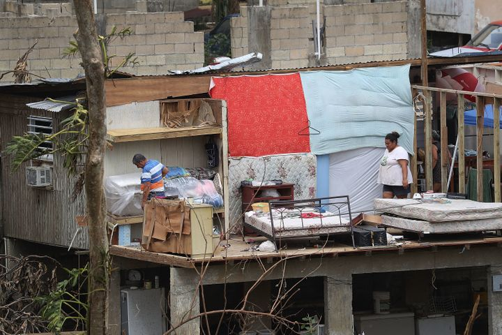 Jose Bernard and his daughter Yolymar salvage what they can from their home in Corozal, Puerto Rico, on Wednesday.