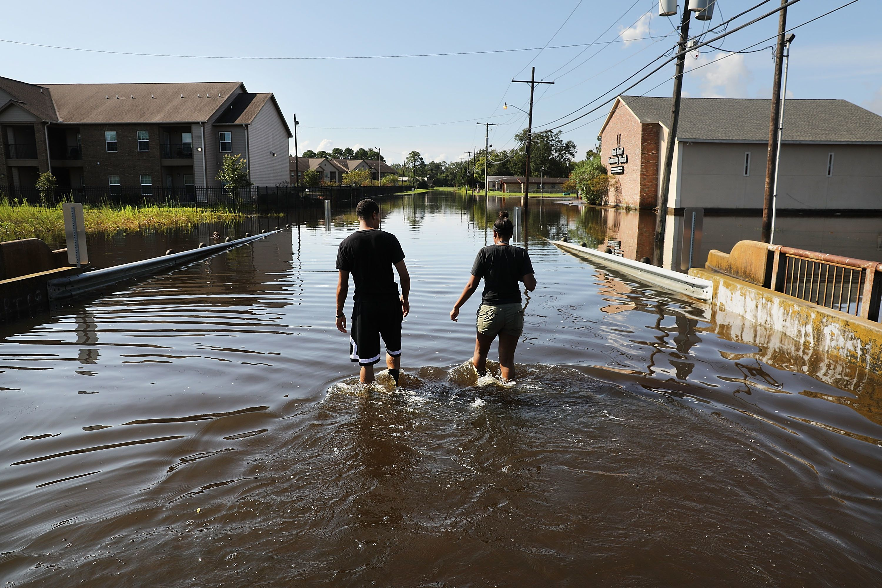 ORANGE, TX - SEPTEMBER 05: A couple walk through their flooded neighborhood as Texas slowly moves toward recovery from the devastation of Hurricane Harvey on September 5, 2017 in Orange, Texas. Almost a week after Hurricane Harvey ravaged parts of the state, some neighborhoods still remained flooded and without electricity. While downtown Houston is returning to business, thousands continue to live in shelters, hotels and other accommodations as they contemplate their future.  (Photo by Spencer Platt/Getty Images)
