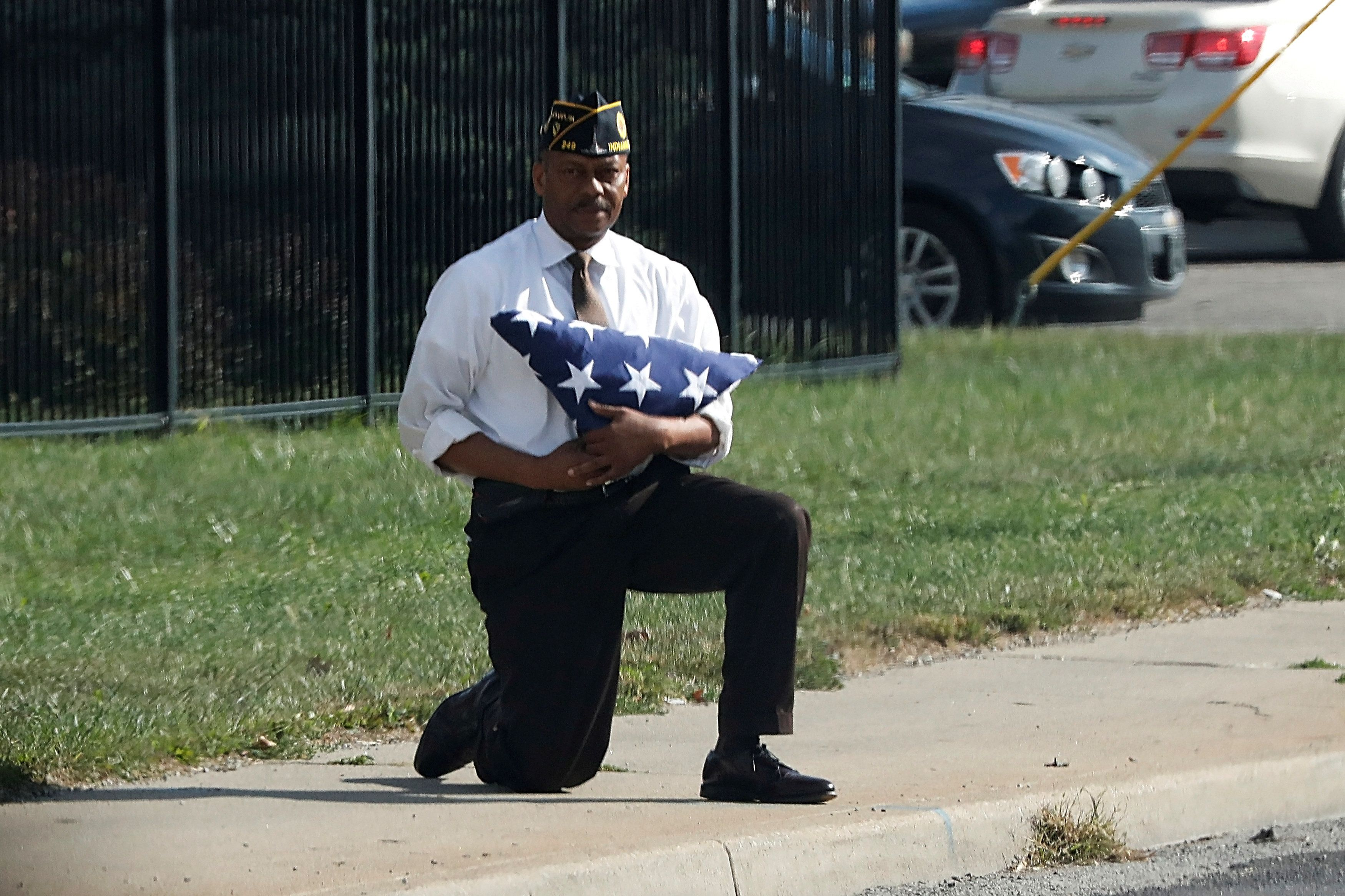 A man kneels with a folded U.S. flag as the motorcade of U.S. President Donald Trump passes him after an event at the state fairgrounds in Indianapolis, Indiana, U.S. September 27, 2017. REUTERS/Jonathan Ernst     TPX IMAGES OF THE DAY