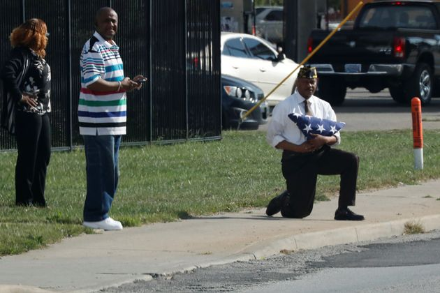 Marvin L. Boatright, as seen from President Donald Trump's motorcade, takes a knee while holding a folded...
