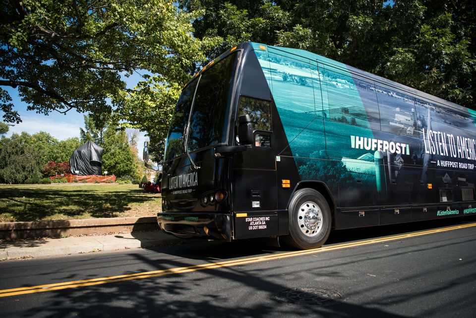 The HuffPost bus sits in front of the Robert E. Lee statue, which is covered in plastic, in Charlottesville, Virginia, on Sep