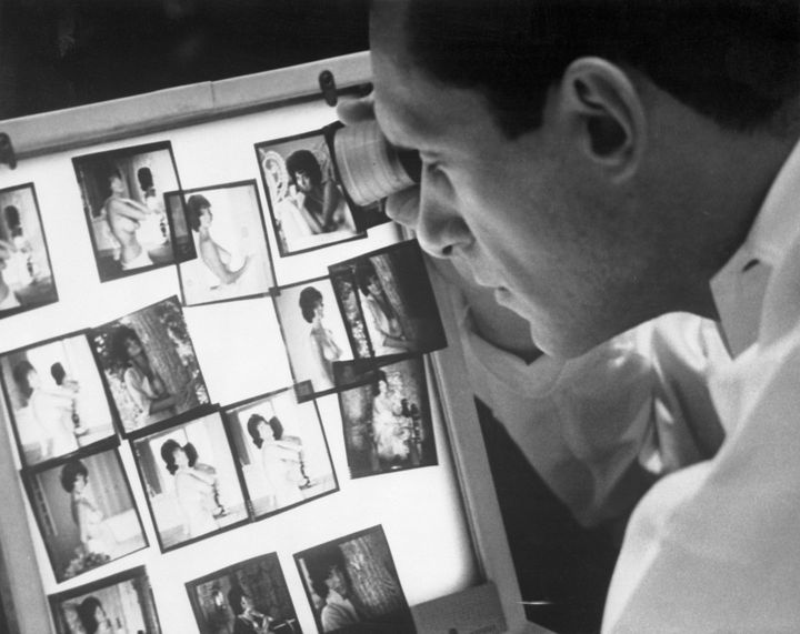 Hugh Hefner viewing photographs in his Chicago office.