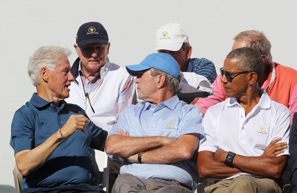 As Clinton chats, Bush and Obama are among those listening.