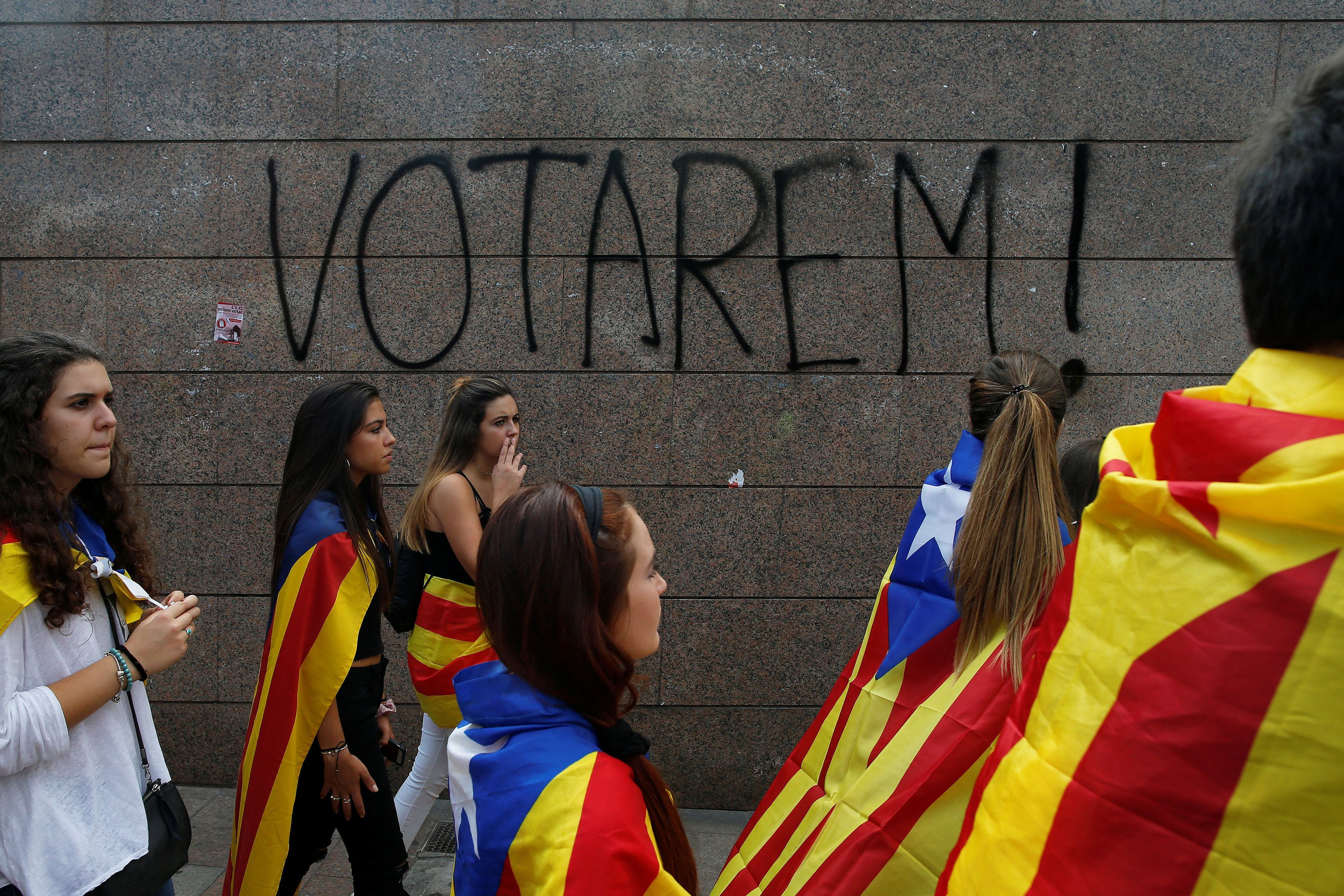 "Students wear Esteladas (Catalan separatist flag) during a demonstration in favor of the banned October 1 independence referendum in Barcelona, Spain September 28, 2017. The graffiti on the wall reads, ""We will vote!"". REUTERS/Jon Nazca"