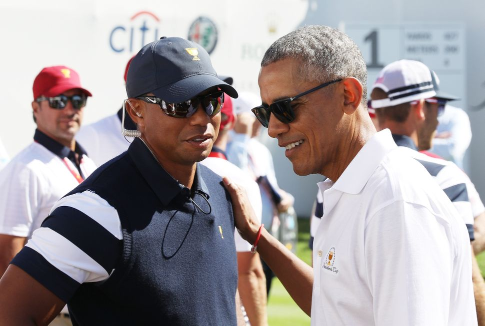 Tiger Woods, a captain's assistant for the U.S. team, talks with Obama.
