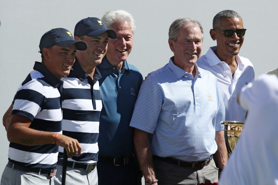Golfers Rickie Fowler and Justin Thomas of the U.S. team pose for a photo with the three ex-presidents.