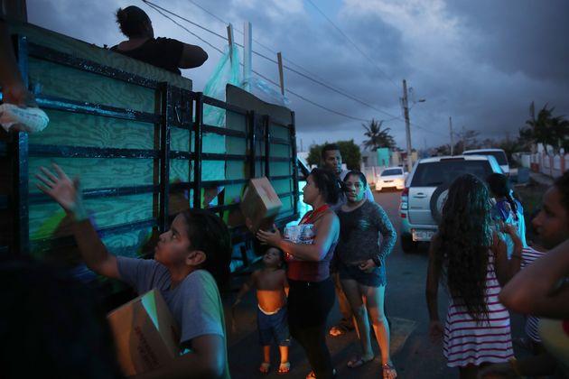 Supervivientes del huracán recibiendo alimentos y agua distribuidos por voluntarios y por la Policía,...