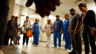 SAN JUAN, PUERTO RICO - SEPT. 26, 2017: Hospital employees and nurses gather to pray for a co-worker who was critically injured in a violent attack during the chaos post-Maria hurricane. At the Centro Medico Puerto Rico (hospital), critical care cases from all over the island are brought for care. It has been a struggle to keep everything working smoothly given the damage done to infrastructure. (Photo by Carolyn Cole/Los Angeles Times via Getty Images)