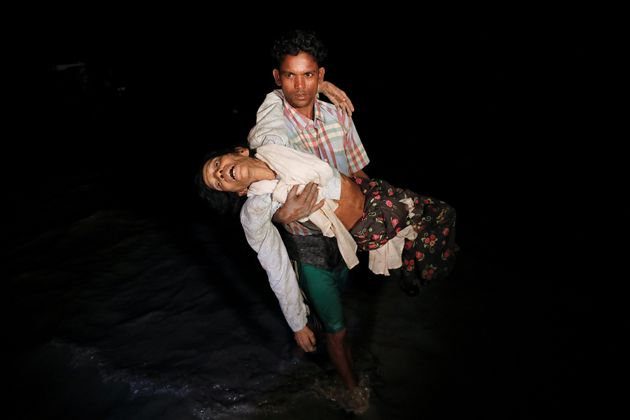 Nobi Hossain wades through the water carrying his elderly relative, Sona Banu, as hundreds of Rohingya...