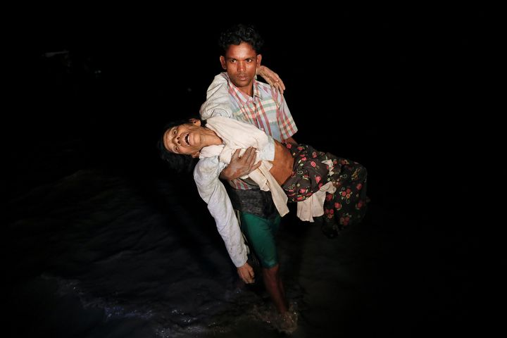 Nobi Hossain wades through the water carrying his elderly relative, Sona Banu, as hundreds of Rohingya refugees arrive by woo