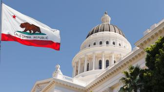 California State Capitol building with state flag in Sacramento on a windy summer day with clear sky