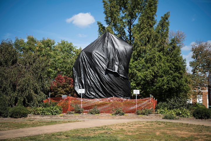 The statue of Confederate Gen. Robert E. Lee that sparked protests in August sits covered in plastic in Charlottesville, Virg